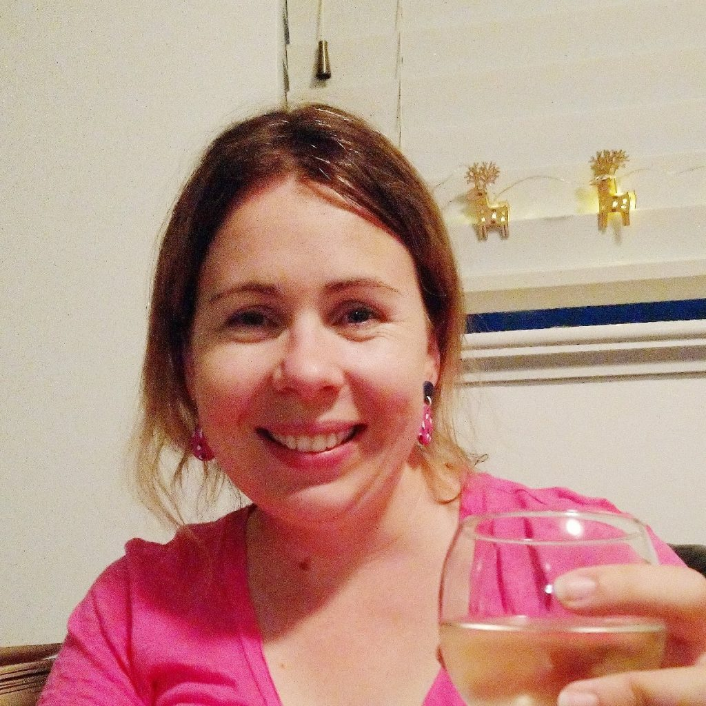 Linda smiling with a glass of wine