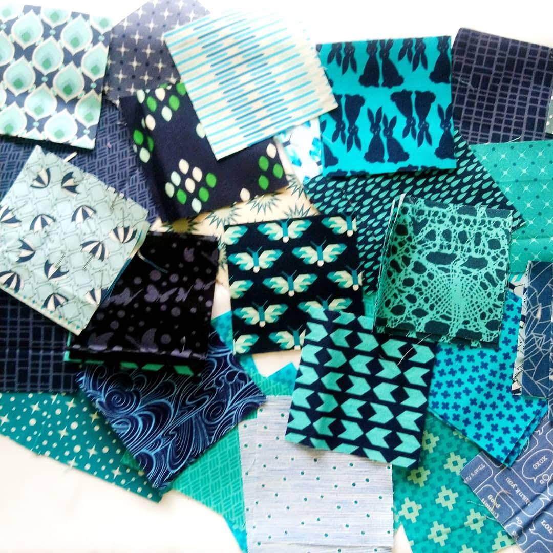 Randomly arranged fabric swatches in varying shades of blues and greens.