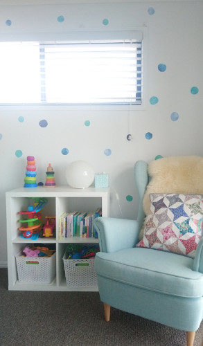 Progress shot of the reading chair and toy storage in the room with the wall stickers added