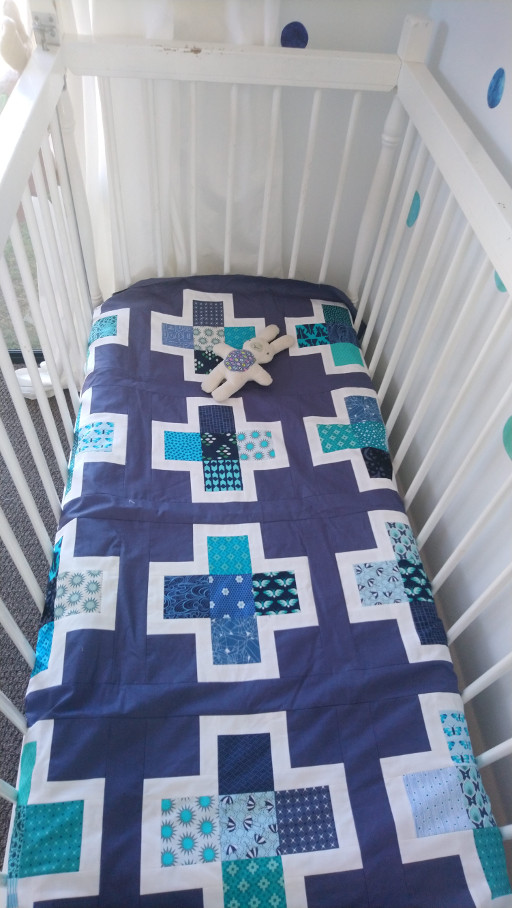 Hugo Room Reveal cot with quilt tucked in