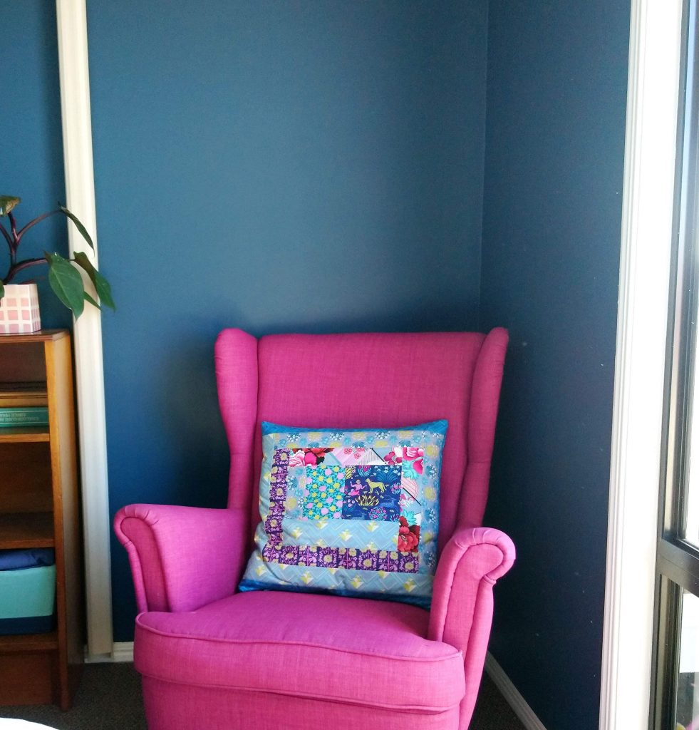 The pink chair with the blue walls.