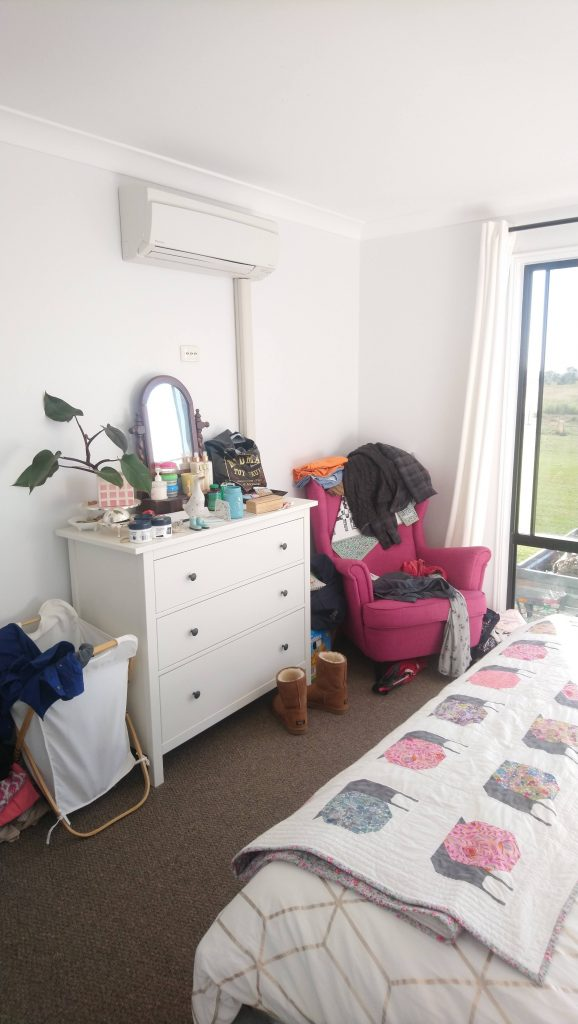 Standing in ensuite doorway looking at dresser and chair wall, very cluttered and messy.