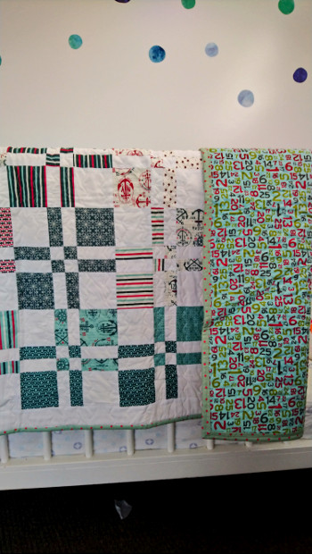 Quilt hanging on cot rail with backing folded back.