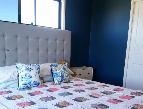 Bedroom painted dark blue showing snail quilt on bed and bedside table.