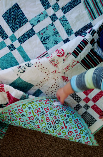 Quilt swirl on floor with blury baby Hugo hand