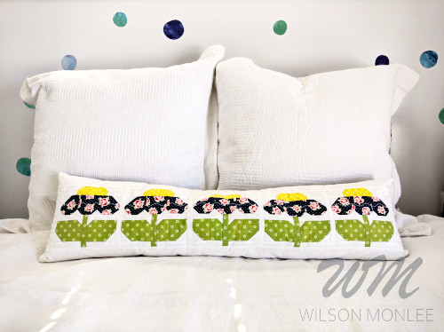 full width shot of finished blue zinnia cushion on guest bed with white euro cushions behind.
