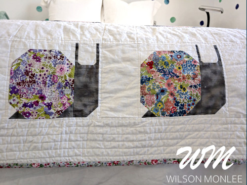 Close up of two floral snails and quilting of the border of the quilt.