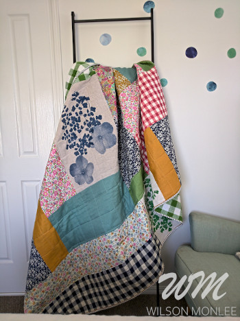 quilt draped over quilt ladder in guest room.