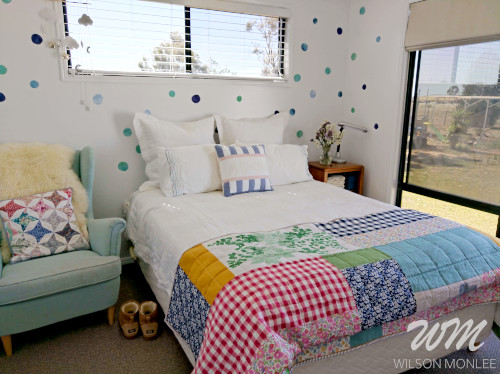 wide shot of guest room with quilt folded back across the end of the bed.