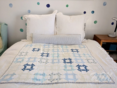 Full churn dash quilt on guest bed