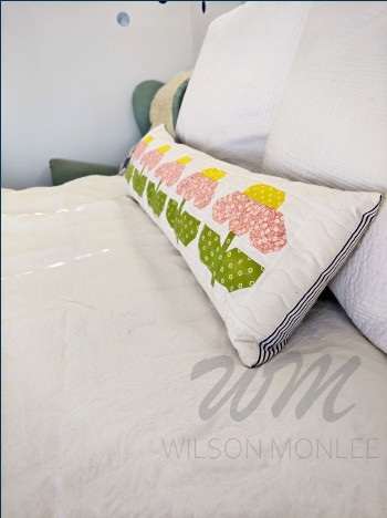 Angled shot of pink zinnia cushion showing peek of blue and white striped backing fabric