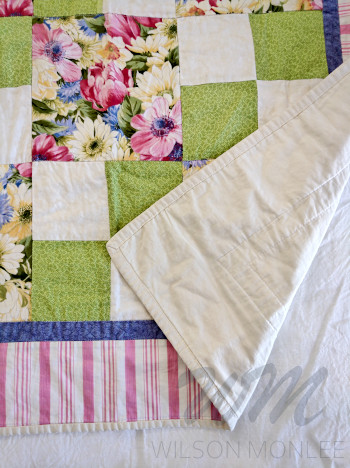 First quilt with corner flipped to show backing and that quilting was in the ditch.